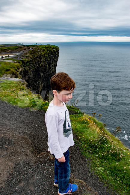 Boy looking out up the Cliffs of Moher Tourist Attraction in Ireland Stock Photo