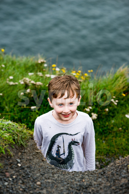 Boy looking up the Cliffs of Moher Tourist Attraction in Ireland Stock Photo