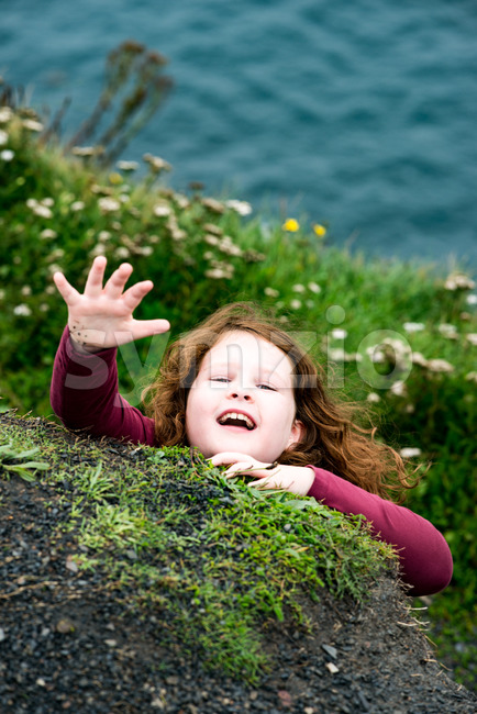 Girl looking up the Cliffs of Moher Tourist Attraction in Ireland Stock Photo