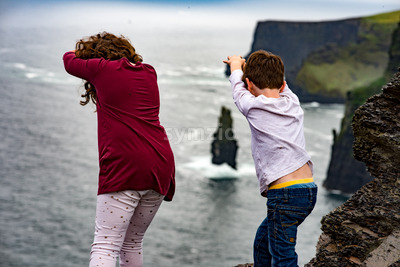 Girl and Boy pretending to dive off the Cliffs of Moher Tourist Attraction in Ireland Stock Photo