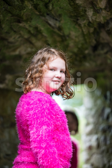 Young little girl portrait looking and smiling at the camera while exploring in an old castle Stock Photo