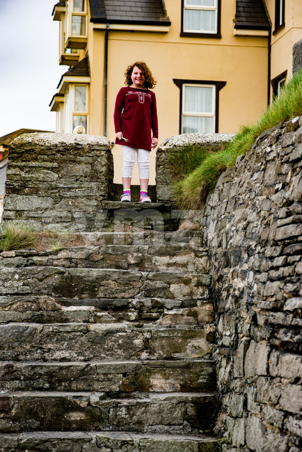 Young little girl portrait looking and smiling standing at top of rocky stairs Stock Photo