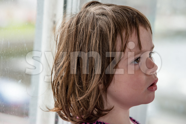 View of Young little girl portrait looking out window