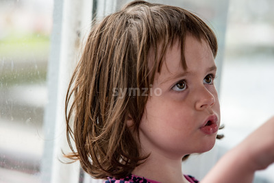 Young little girl portrait looking out window Stock Photo