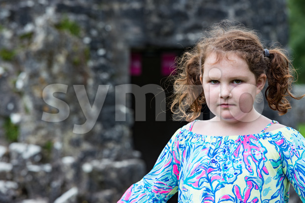 View of Young little girl portrait looking at the camera with Aughnanure castle in background