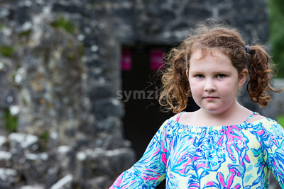 Young little girl portrait looking at the camera with Aughnanure castle in background Stock Photo