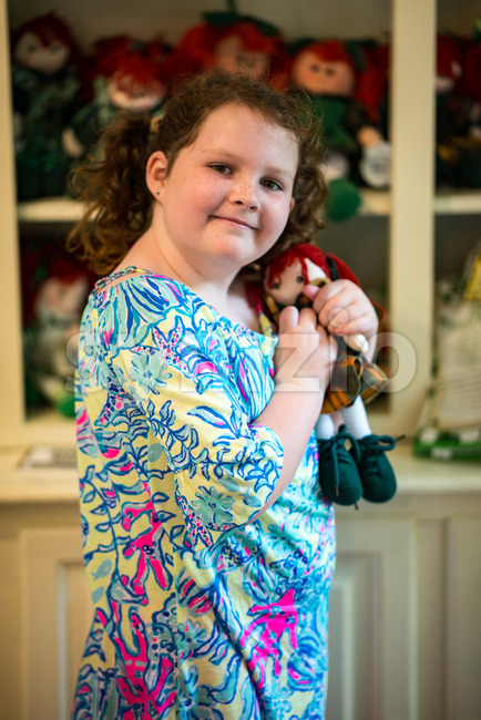 Young little Irish red-headed girl portrait looking and smiling at the camera holding doll that looks like herself Stock Photo