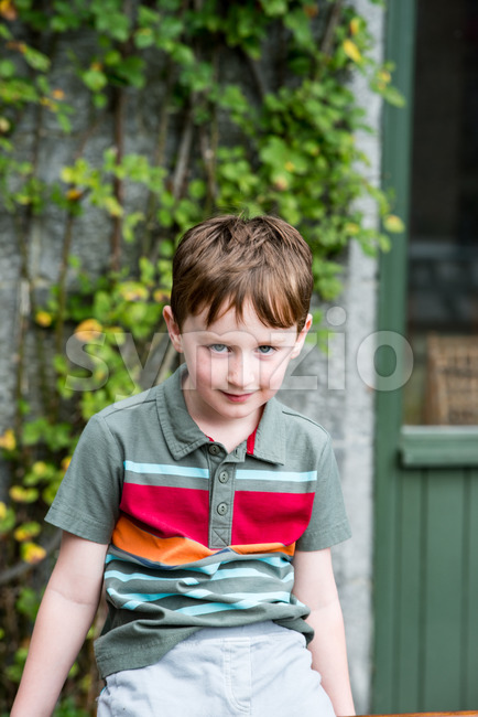 Young little boy portrait sitting down looking at camera Stock Photo