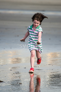 Young little girl on beach playing in the surf Stock Photo