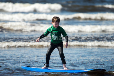 Young little boy on beach taking surfing lessons Stock Photo