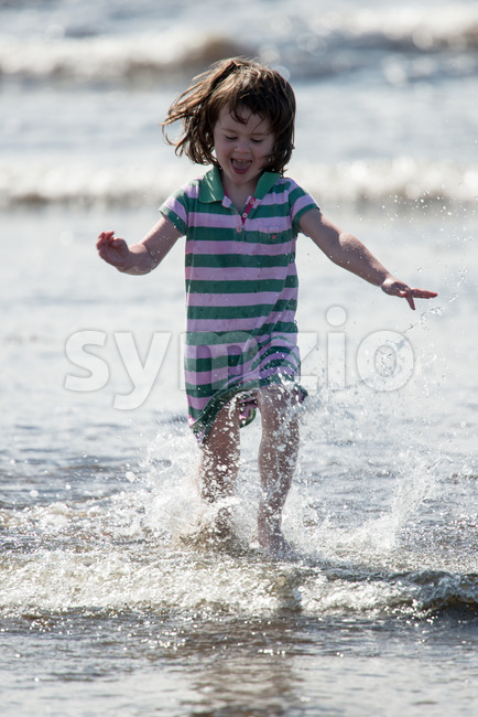 View of Young little girl on beach playing in the surf