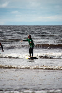 Young little girl on beach taking surfing lessons Stock Photo