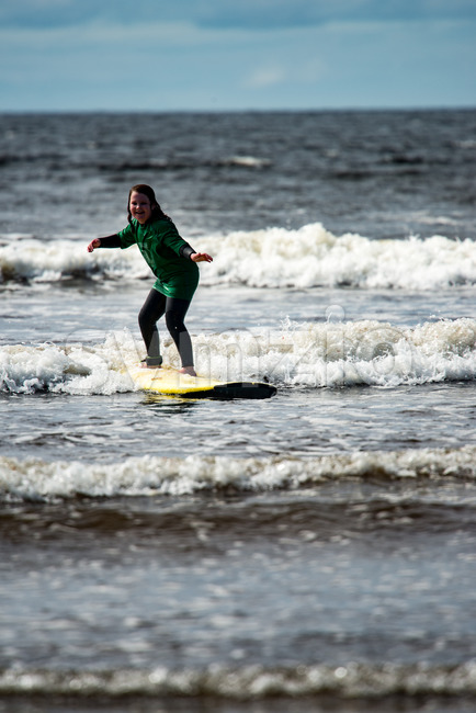 View of Young little girl on beach taking surfing lessons