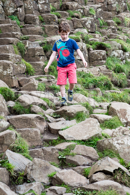 Young Boy walking on the rocks at Giant's Causeway Stock Photo