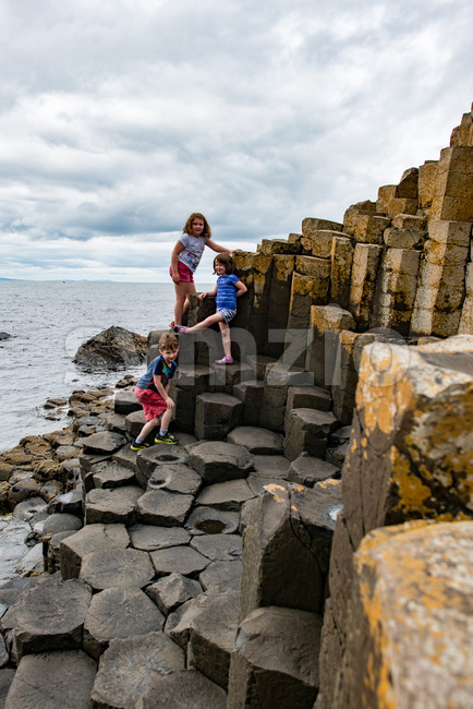View of Siblings climbing the rocks at Giant's Causeway