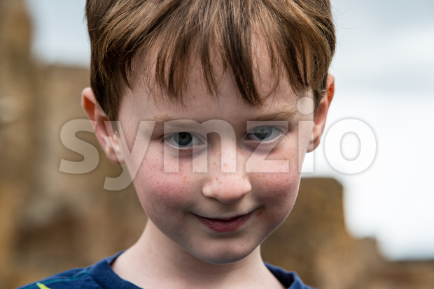 View of Young little boy portrait looking and smiling at the camera.
