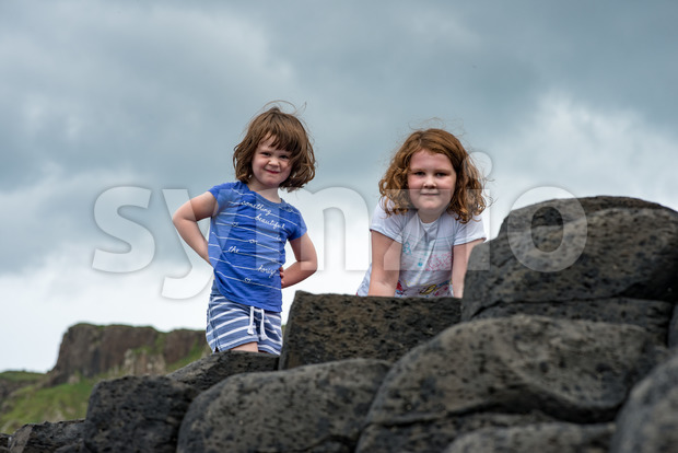 Siblings climbing the rocks at Giant's Causeway Stock Photo