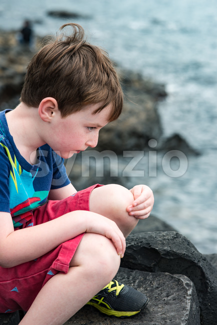 Boy sitting on the rocks at Giant's Causeway Stock Photo