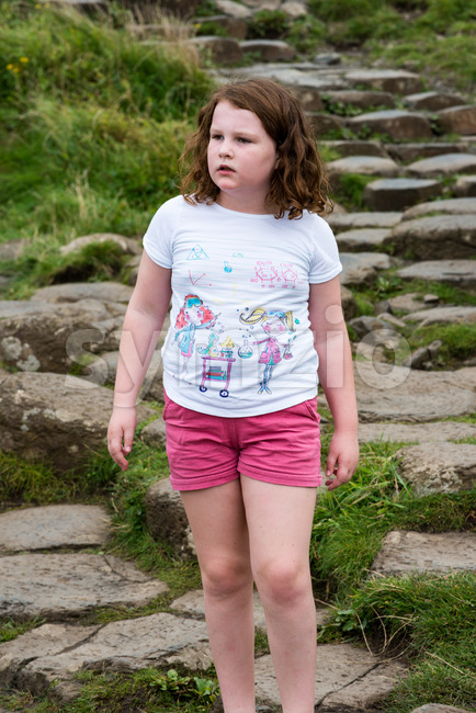 Young Girl walking on the rocks at Giant's Causeway Stock Photo