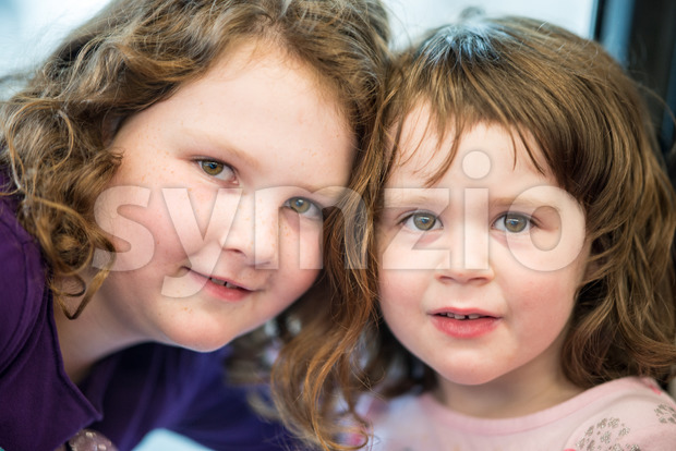 Young sibling girls portrait looking and smiling at the camera. Stock Photo