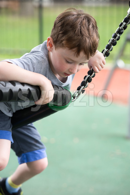 Young boy having fun outside at park on a playground climbing set Stock Photo