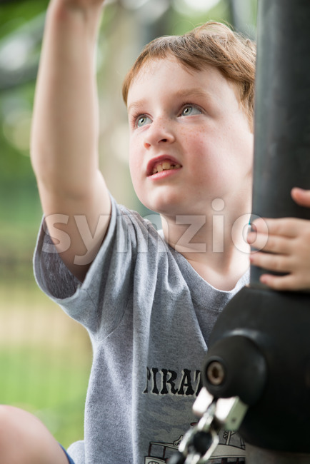 View of Young boy having fun outside at park on a playground climbing set