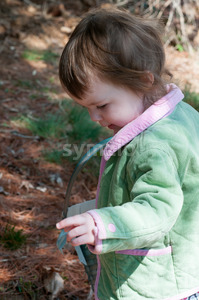 Young little toddler girl with basket searching for easter eggs Stock Photo