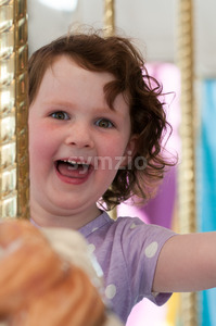Young girl riding on fairground horse on carousel amusement ride at fairgrounds park outdoor Stock Photo