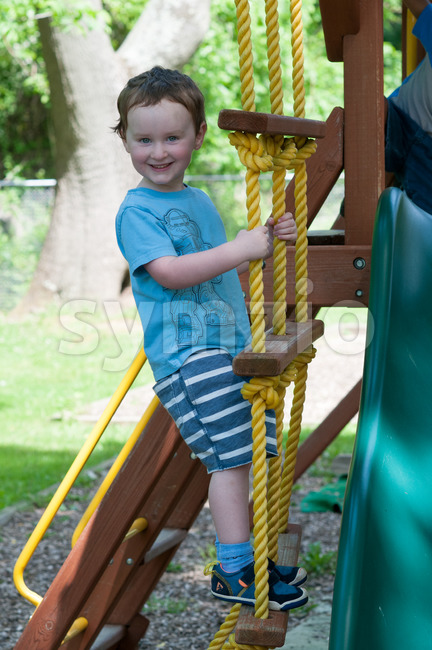 View of Happy little child boy climbing on the rope ladder outside