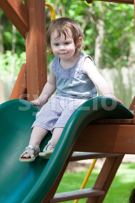 Girl riding on childrens slides on playground Stock Photo