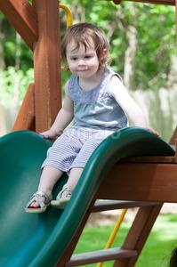 Girl riding on childrens slides on playground Stock Photo