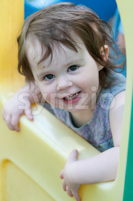 View of Little girl wearing summer dress looking out from plastic play house window in a playground