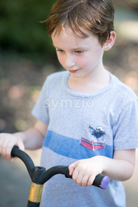 Young litte boy outside riding his scooter in the driveway Stock Photo