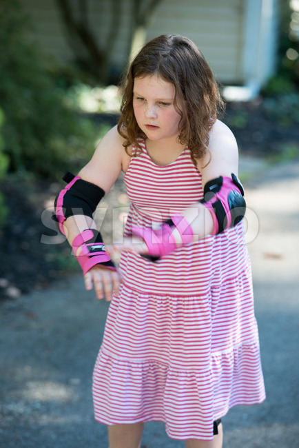 View of Young girl outside learning to riding on roller skates on driveway wearing protective elbow, wrist and knee pads