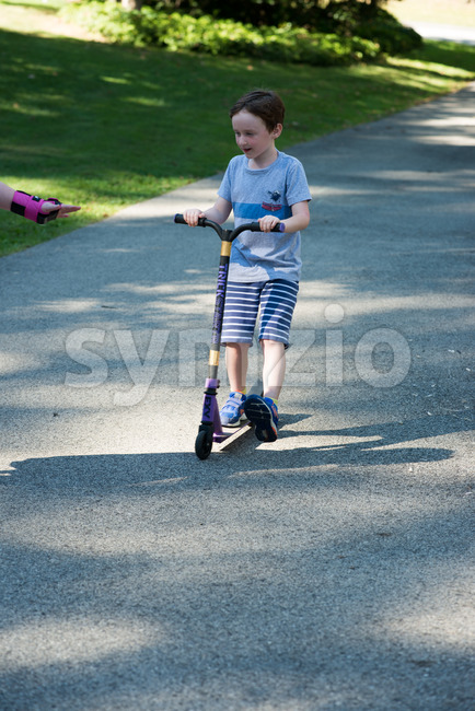 View of Young litte boy outside riding his scooter in the driveway