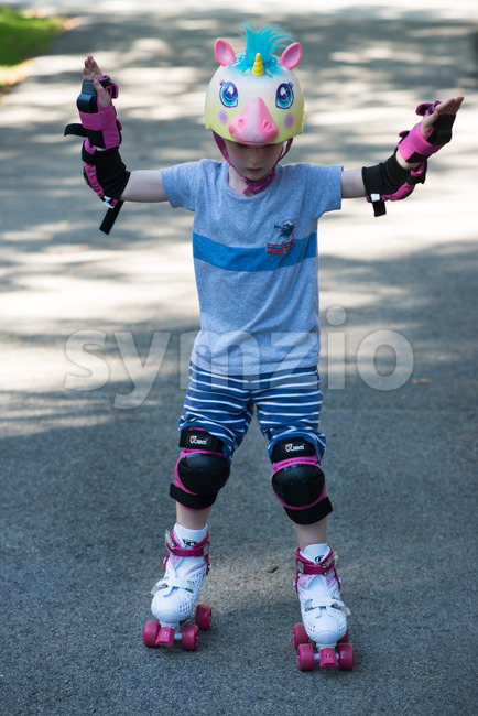 Young boy outside learning to riding on roller skates on driveway wearing protective helmet and elbow, wrist and knee pads Stock Photo