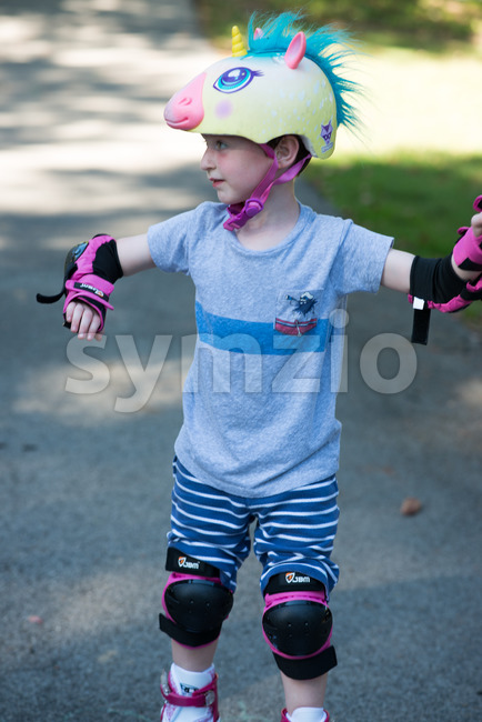 View of Young boy outside learning to riding on roller skates on driveway wearing protective helment and elbow, wrist and ...