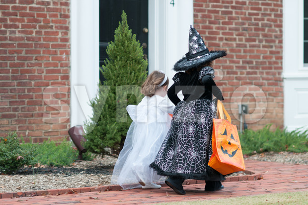 View of Little girls in witch and ghost costume having fun at Halloween trick or treat