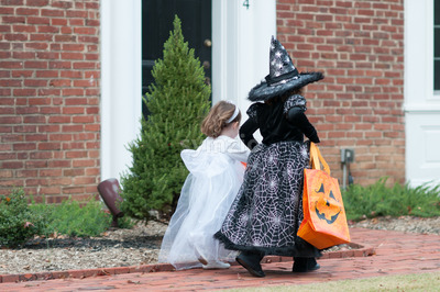 Little girls in witch and ghost costume having fun at Halloween trick or treat Stock Photo