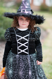 Little girl in witch costume having fun at Halloween trick or treat Stock Photo
