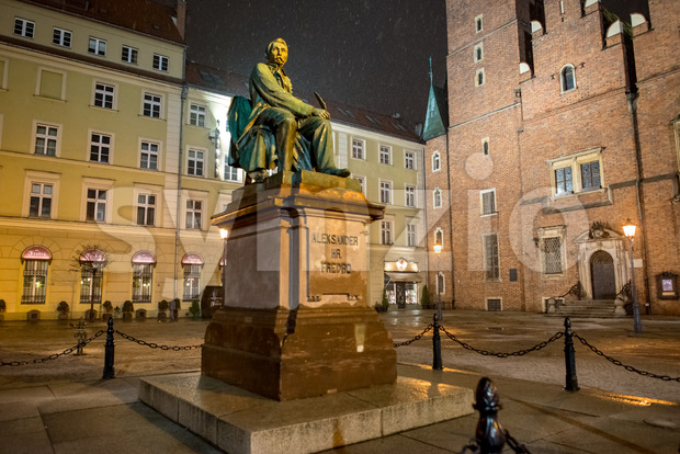 Wroclaw, Poland - March 6, 2018: Neoclassical bronze statue of famous Polish writer Alexander Fredro, 1897, by Leonard Marconi at night, Market Square Stock Photo