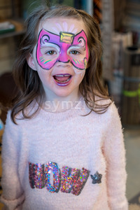 Pretty excited cute young girl with face painting like a butterfly Stock Photo