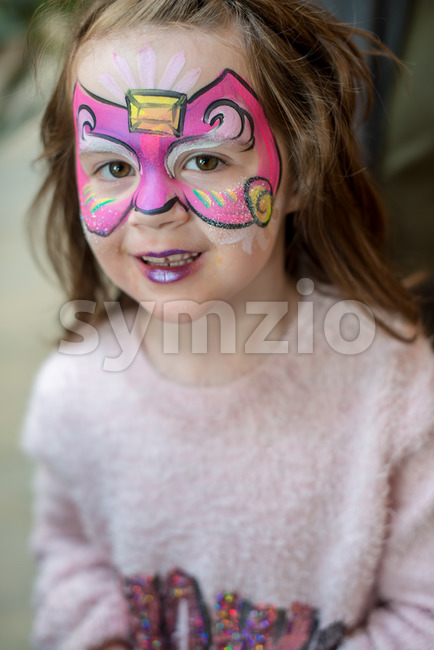 View of Pretty excited cute young girl with face painting like a butterfly