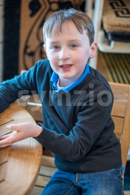 handsome young boy sits in chair all dressed up for Easter holidays Stock Photo