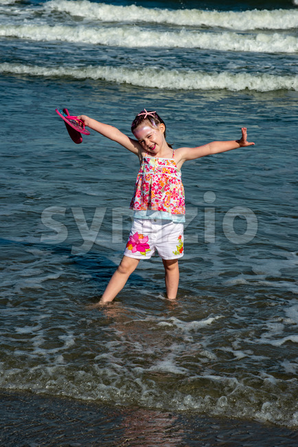 View of Portrait of a beautiful young mermaid girl playing in the ocean surf at the beach on a sunny ...