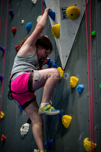 Young girl climbing up on practice wall in indoor rock gym Stock Photo
