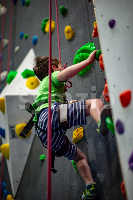 View of Young boy climbing up on practice wall in indoor rock gym