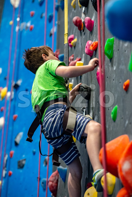 Young boy climbing up on practice wall in indoor rock gym Stock Photo