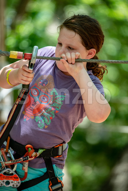 View of Portrait of a beautiful girl on a rope park among trees. Children summer activities.