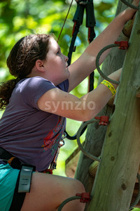 Portrait of a beautiful girl on a rope park among trees. Children summer activities. Stock Photo